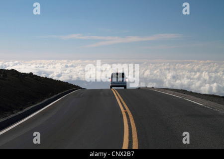 passenger car on a road over the clouds on top of the volcano Haleakala (3000 m), USA, Hawaii, Maui - Stock Photo