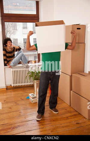 A man with a box on his head flexing his muscles while woman watches - Stock Photo