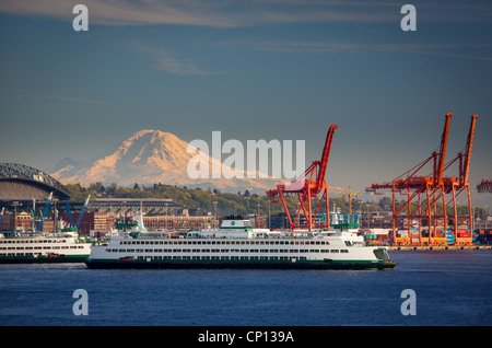 Washington state ferry in Seattle harbor with Mount Rainier in the distance - Stock Photo