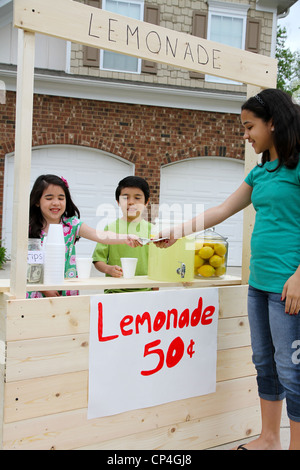 Children selling lemonade in front of their home - Stock Photo