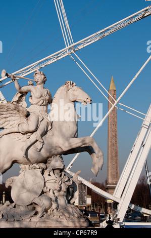 Ferris wheel on the Place de la Concorde and Tuileries Garden sculptures in Paris France - Stock Photo