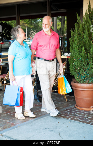 Senior couple out shopping together. (word visible in window is just 'sangria', not restaurant name or logo) - Stock Photo