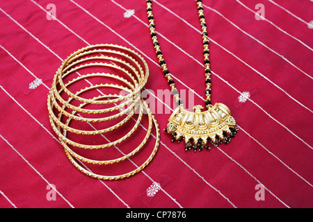 Traditional Indian gold jewelry on red silk fabric - Stock Photo