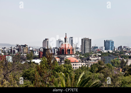 view of Mexico City skyline on spring day looking South from Chapultepec hill over treetops of Chapultepec park - Stock Photo