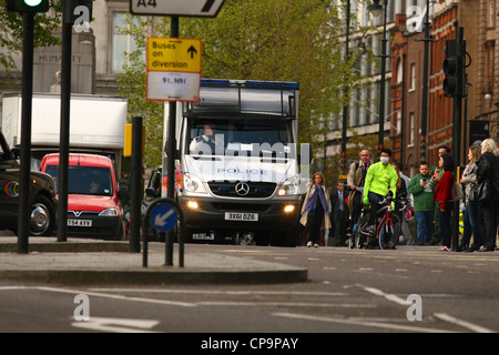 Front view of a Police van and other traffic waiting at a set of traffic lights in London - Stock Photo