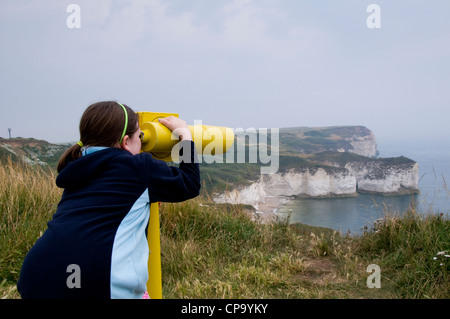 A young girl looking through a coin-operated telescope at Flamborough Head. - Stock Photo