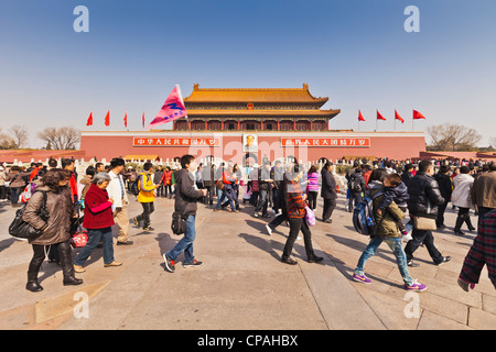 Chinese tourists and tour guide walking outside the Tian'anmen Gate, the Gate of Heavenly Peace, entrance to the - Stock Photo