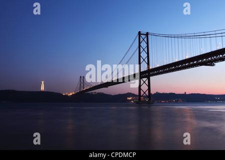 The 25 April Suspension Bridge at dusk over the River Tagus (Rio Tejo), Christus Rei is illuminated at Almada, Lisbon, - Stock Photo