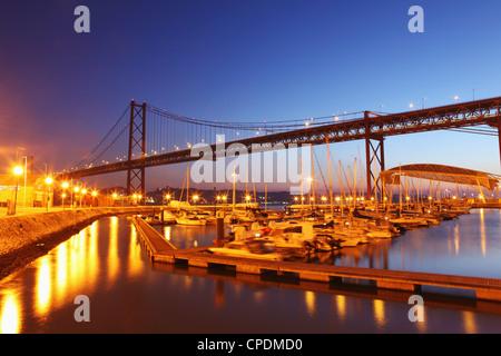Boats on the River Tagus move at night in the Doca de Santa Amaro marina under the 25 April Bridge, Lisbon, Portugal, - Stock Photo