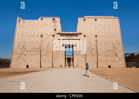 Man standing by the entrance pylon of the Temple of Horus, Edfu, Egypt, North Africa, Africa - Stock Photo