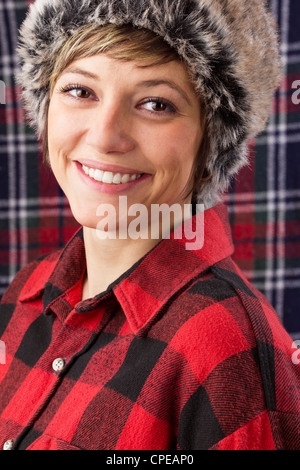 Wonderful smiling young woman wearing red and black checked lumberjack shirt and fur hat. Studio shot as close up - Stock Photo