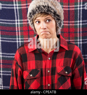 Skeptical pouting young woman wearing a checkered lumberjack shirt and fur hat. Funny studio shot against a patterned - Stock Photo