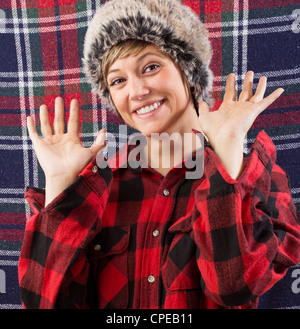 Smiling young woman wearing checkered lumberjack shirt and fur hat waving with both hands at the camera. Funny studio - Stock Photo