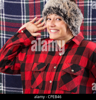 Smiling young woman wearing lumberjack shirt and fur hat posing and waving with her hand at the camera. Funny studio - Stock Photo