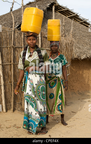 Women carrying water on their heads in Guludo village in the Quirimbas National Park in northern Mozambique. - Stock Photo