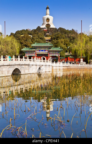 The White Pagoda in Beihai Park, Beijing, China, reflected in the lake on a sunny day in early spring. - Stock Photo