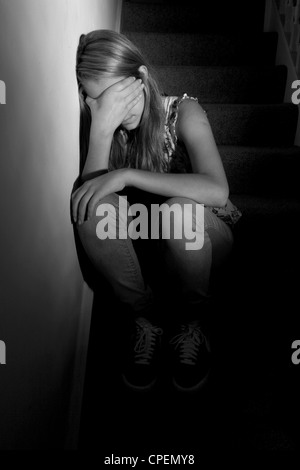 Young girl sitting on dark stairs back view - Stock Photo