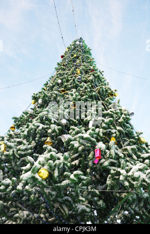 high beautifully decorated with balls and bells cristmas tree outdoors - Stock Photo
