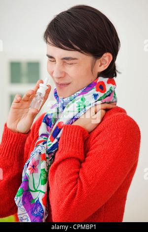 WOMAN USING NOSE SPRAY - Stock Photo