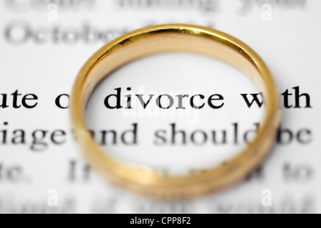 Wedding ring on top of solicitors letter highlighting the words divorce, concept of separation and divorce - Stock Photo