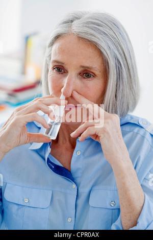 ELDERLY PERSON USING NOSE SPRAY - Stock Photo