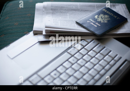 Laptop, newspaper and passport, close up - Stock Photo