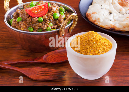 Curry powder with a beef mince curry, keema matar with peas, and naan bread. - Stock Photo