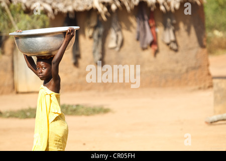 A girl who doesn't go to school heads out to fetch water in the village of Djorbana, Zanzan region, Cote d'Ivoire - Stock Photo