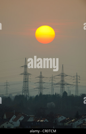 Electric power transmission lines, electricity pylons, with the setting sun, Korb near Stuttgart, Baden-Wuerttemberg - Stock Photo