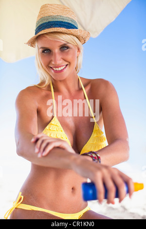 Woman applying sunscreen on beach - Stock Photo
