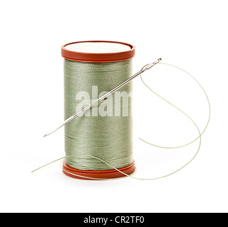 Spool of thread with needle for sewing on white background - Stock Photo