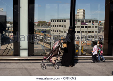 Veiled muslim mother with children on the walkway between Stratford station and the Westfield Shopping Centre, east - Stock Photo