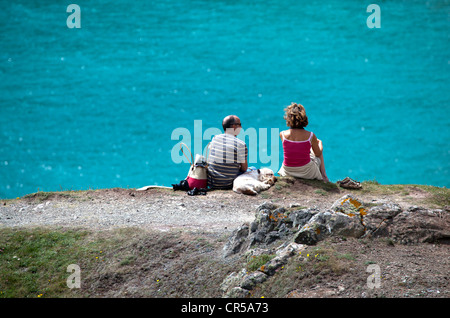 Couple with Dog sitting on clifftop above Kynance Cove - Stock Photo
