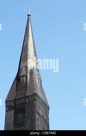 Curious black net shrouded Christian church steeple against blue sky - Stock Photo