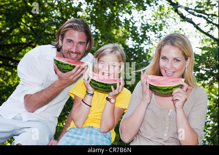Austria, Salzburg County, Family eating watermelons - Stock Photo