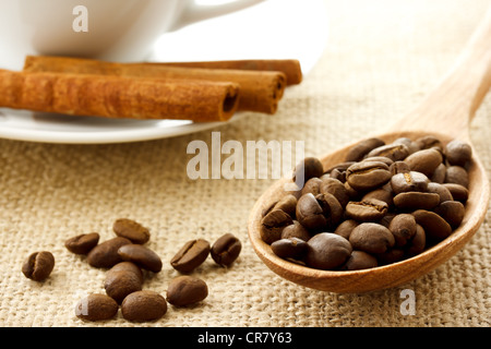 Coffee Beans in a Wooden Spoon with Cinnamon Sticks and Coffee Mug - Stock Photo