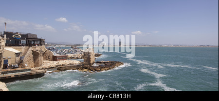 Panoramic view showing a seaside restaurant, harbor, and Bay of Haifa in Acre, Israel - Stock Photo
