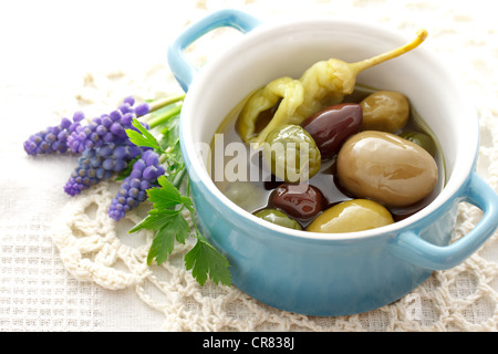 Olives in olive oil with fresh herbs - Stock Photo