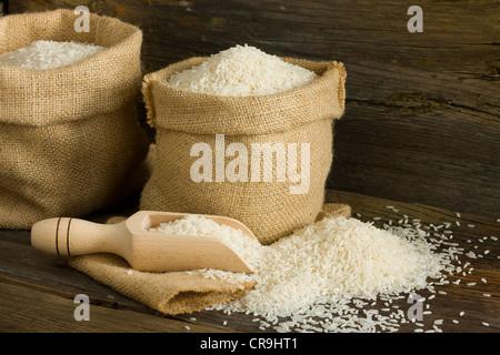 White uncooked rice in burlap bag - Stock Photo