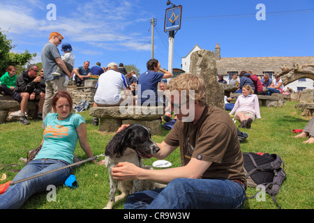 Authentic scene with people sitting in busy beer garden of Square and Compass country village pub lifestyle in summer - Stock Photo