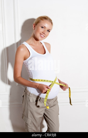 Pregnant woman measuring her belly - Stock Photo