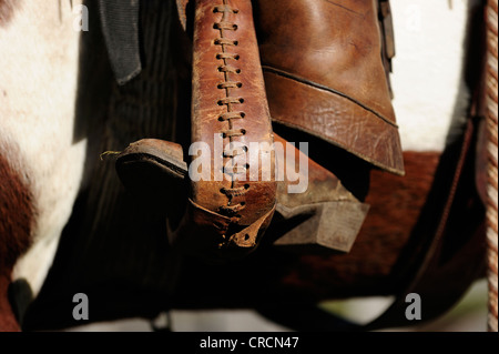 Cowboy boot in a stirrup - Stock Photo
