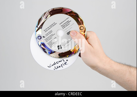 Hand holding an original CD or DVD and a pirate copy of Microsoft Windows Vista - Stock Photo