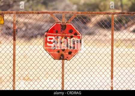 Rusty stop sign with bullet holes - Stock Photo