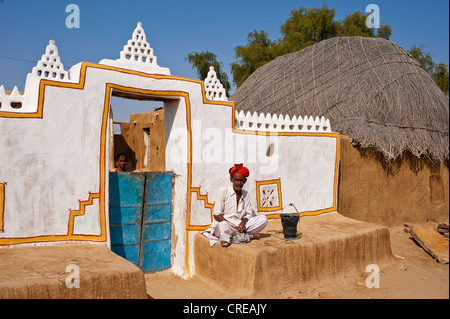 Rajasthani, Indian man wearing a dhoti and turban, sitting in front of his traditionally built and painted front - Stock Photo