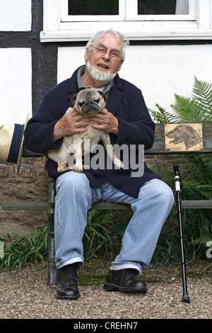 Pug (Canis lupus f. familiaris), old man sitting on a bench in the garden with a Pug, 11 years old - Stock Photo