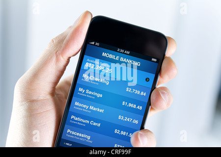 A man holding smart phone with mobile banking application on a screen. Closeup shot. - Stock Photo