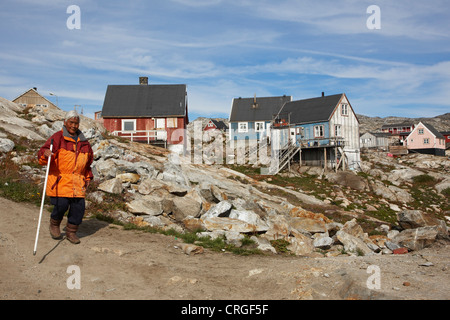 elderly inuit woman in front of wooden houses, Greenland, Ammassalik, East Greenland, Tiniteqilaq - Stock Photo