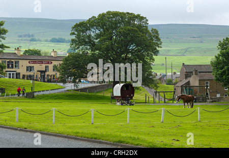 Bainbridge, Wensleydale. A traditional gypsy caravan is parked on the village green with the horse grazing nearby. - Stock Photo