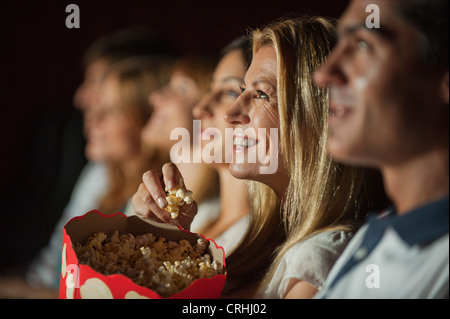 Woman eating popcorn while watching movie in theater - Stock Photo